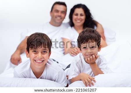 Happy kids with their parents laying in bed on a lazy weekend