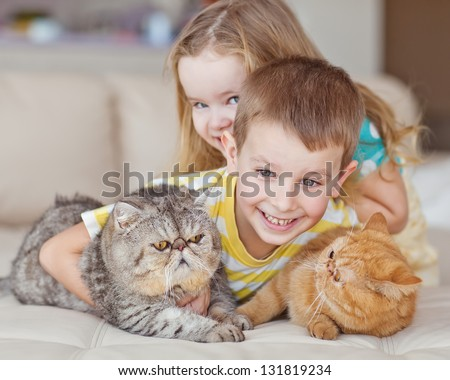 Happy kids with their pets - a cat - stock photo