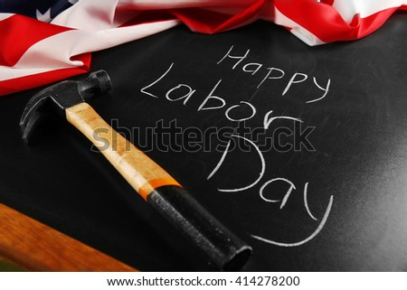 Happy Labor Day text and hammer on blackboard