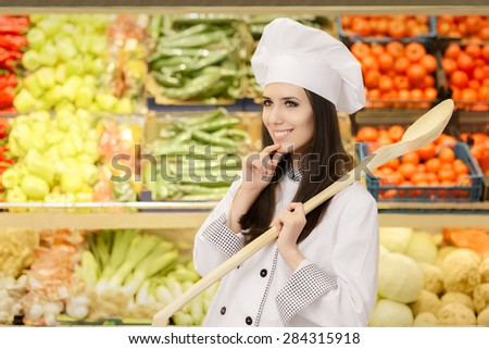 Happy Lady Chef with Big Spoon Making Healthy Menu Options - Young female cook in a grocery store thinking what to buy  - stock photo