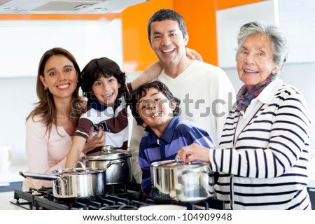 Happy Latin family cooking together at home - stock photo