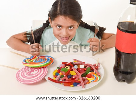 happy Latin female child eating dish full of candy and gummies with fork and knife and big cola bottle in sugar abuse and sweet nutrition excess isolated on white background - stock photo