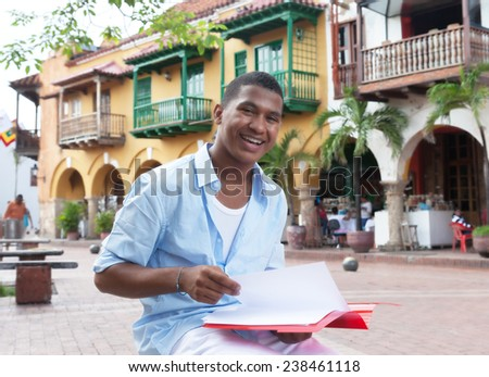 Happy latin student in a colonial town with paperwork - stock photo
