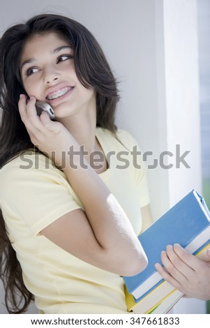 Happy latin teen student with books on the phone