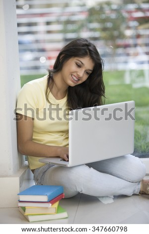 Happy latin teen student with computer