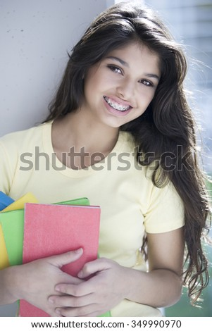 Happy latin teen woman with books