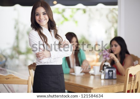 Happy latin waitress greeting customers at a coffee shop
