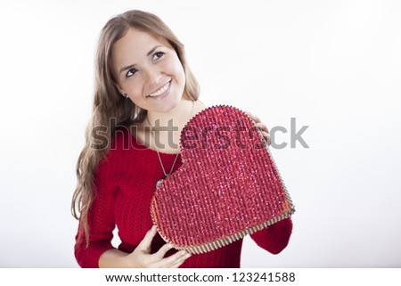 Happy latin woman holding a big heart and looking towards copy space - stock photo