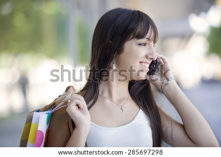 Happy latin woman on the phone with shopping bags