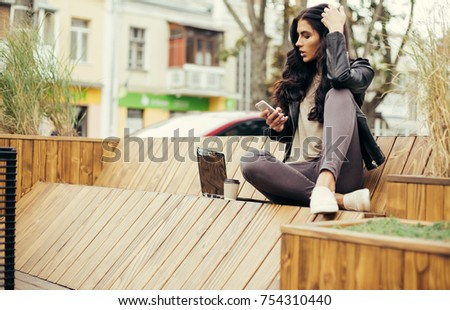 Happy latin woman with smartphone or laptop in city centre