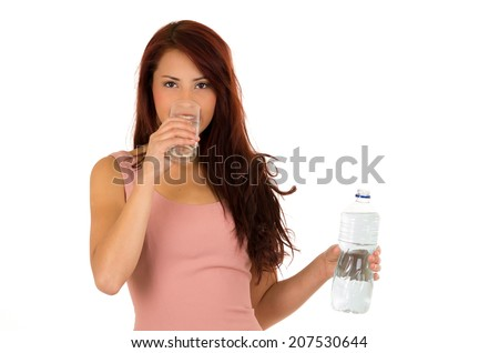 Happy latin young girl holding a bottle and drinking water from glass isolated on white - stock photo