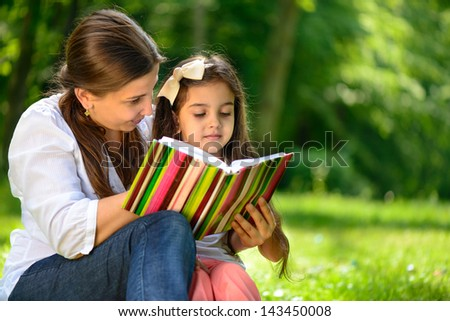Happy latino family reading book at park - stock photo