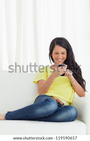 Happy Latino looking her smartphone while sitting on a sofa