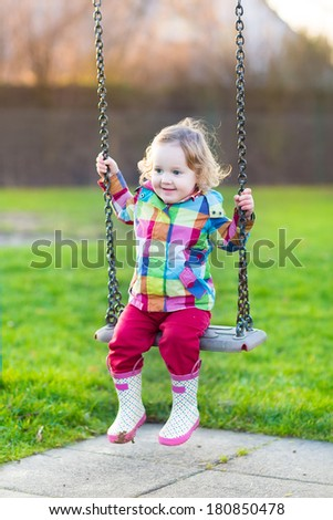 Happy laughing baby girl having fun on a swing in the garden on a sunny spring day - stock photo