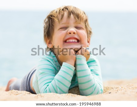 Happy laughing baby girl laying on sand beach - stock photo