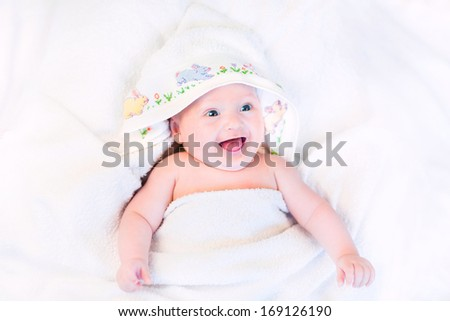 Happy laughing baby in a hand made cross stitch hooded towel after bath - stock photo