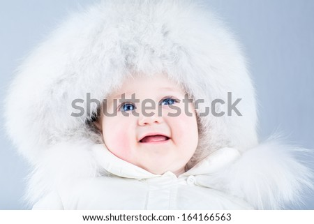 Happy laughing baby in a white winter jacket