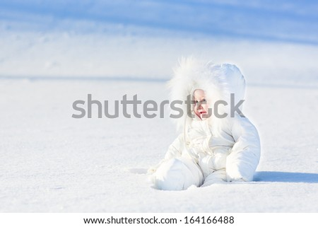 Happy laughing baby playing in snow on a sunny winter day