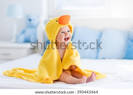 Happy laughing baby wearing yellow hooded duck towel sitting on parents bed after bath or shower. Clean dry child in bedroom. Bathing and washing of little kids. Children hygiene. Textile for infants. - stock photo