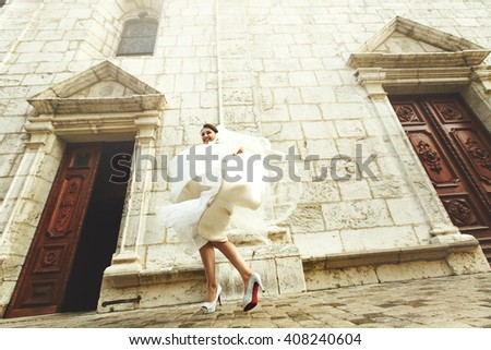 Happy laughing beautiful brunette bride dancing near old french church - stock photo