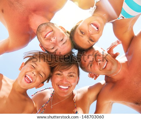 Happy Laughing Big Family Having Fun at the Beach. Enjoying Sun and Summer Holidays. Smiling People standing together in a circle against blue sky  - stock photo