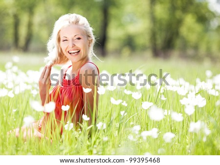 happy laughing blond woman  on the  meadow with white flowers  on a warm summer day - stock photo