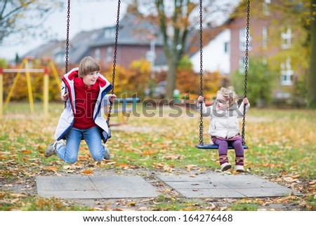 Happy laughing boy and his little baby sister playing together on a swing in autumn - stock photo