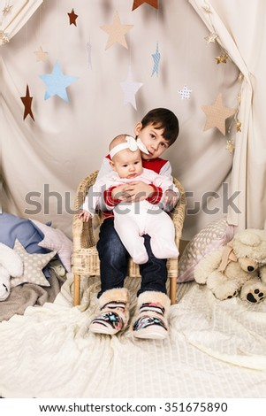 Happy laughing boy holding his newborn baby sister - stock photo