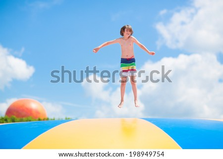 Happy laughing boy jumping on a colorful trampoline having fun at a party in a recreation park during summer vacation - stock photo