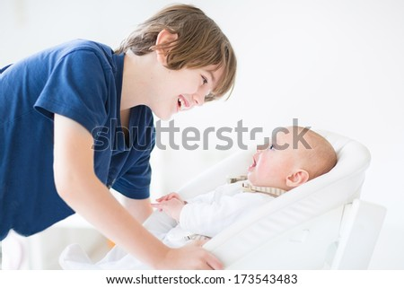 Happy laughing boy talking to his newborn baby brother