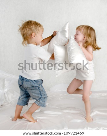 happy laughing brother and sister  having a pillow fight in bed at home