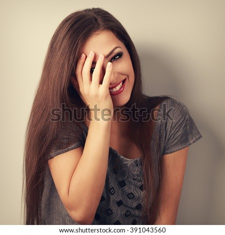 Happy laughing brunette young woman cover the hand her face and giggling. Vintage toned portrait - stock photo