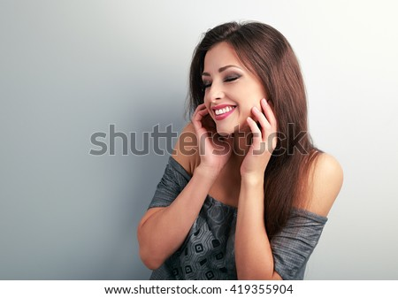 Happy laughing brunette young woman holding the hand at face and giggling on blue background - stock photo