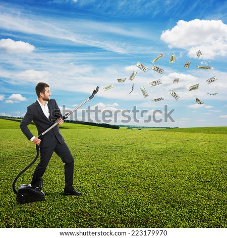 happy laughing businessman holding vacuum and catching paper money at outdoor - stock photo
