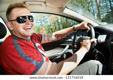 Happy laughing car driver man driving automobile  at summer - stock photo