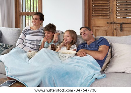 Happy laughing Caucasian family with two children relaxing at home, kids brother and sister watching a movie and having popcorn with parents - stock photo