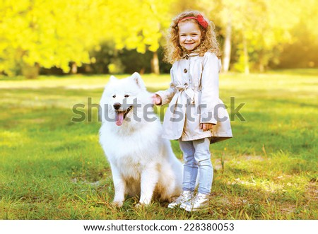 Happy laughing child and dog having fun outdoors in warm autumn day