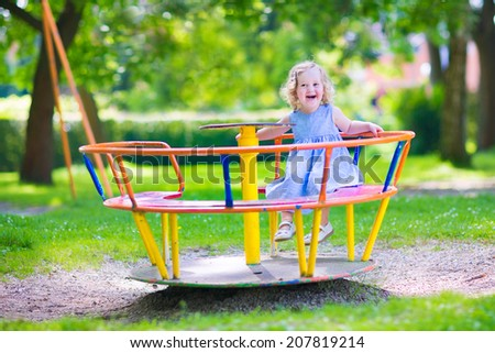 Happy laughing child, beautiful little toddler girl with curly hair wearing a blue dress having fun on a playground enjoying a swing ride on a hot summer day in a sunny city park - stock photo
