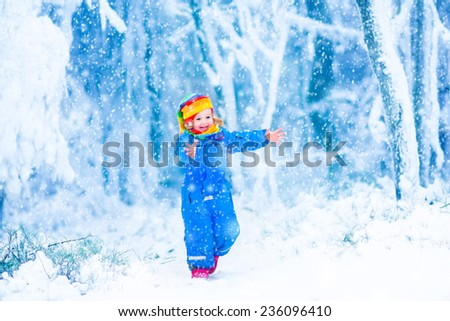 Happy laughing child, cute toddler girl in a colorful snowsuit and hat, running in a snowy winter park catching snow flakes - stock photo