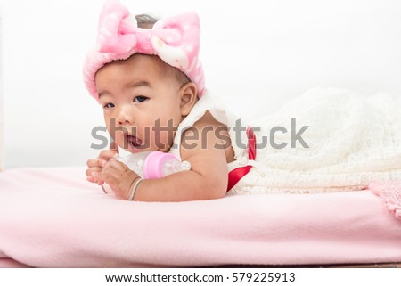 happy laughing child lies with milk bottle on bed.