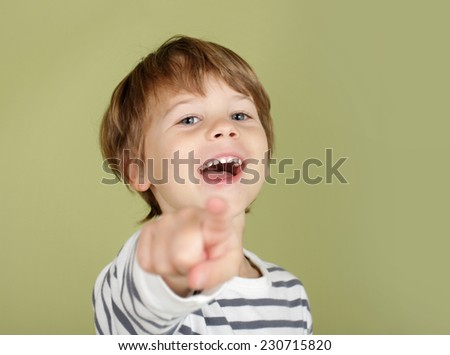 Happy, laughing child pointing straight at viewer