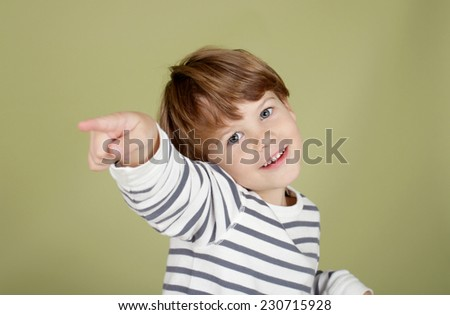 Happy, laughing child pointing straight at viewer - stock photo