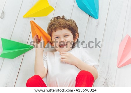 Happy laughing child throwing paper airplane indoors. Happy childhood, travel, vacation concept. Top view.