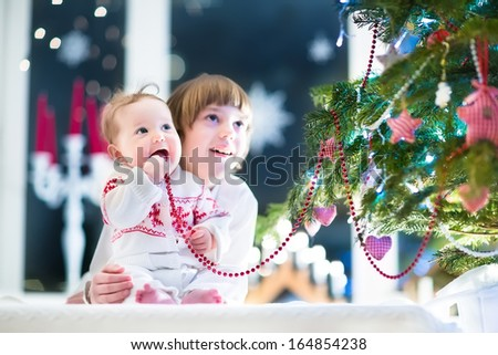 Happy laughing children playing under a beautiful Christmas tree in a dark living room - stock photo