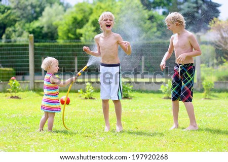 Happy laughing children, two young school boys and adorable toddler girl, enjoying hot sunny summer vacation day playing outdoors in garden at the backyard of the house spraying water from the hose - stock photo
