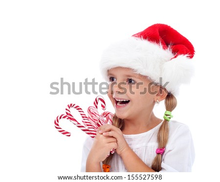Happy laughing christmas hat girl with candy cane sweets - isolated - stock photo