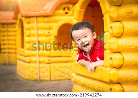 Happy laughing cute little three years old asian child boy or kid playing in a yellow house on a playground. Healthy lifestyles concept.  - stock photo