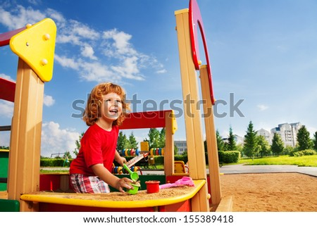 Happy laughing cute little three years old child boy playing in sandbox - stock photo