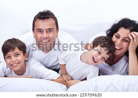 Happy laughing family portrait - parents with two little boys
