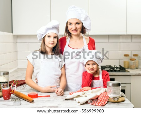 Happy laughing family preparation holiday food. Young beautiful mother and her cute daughter cooking Christmas cookies. concept. Mother and daughter making dough in white kitchen.